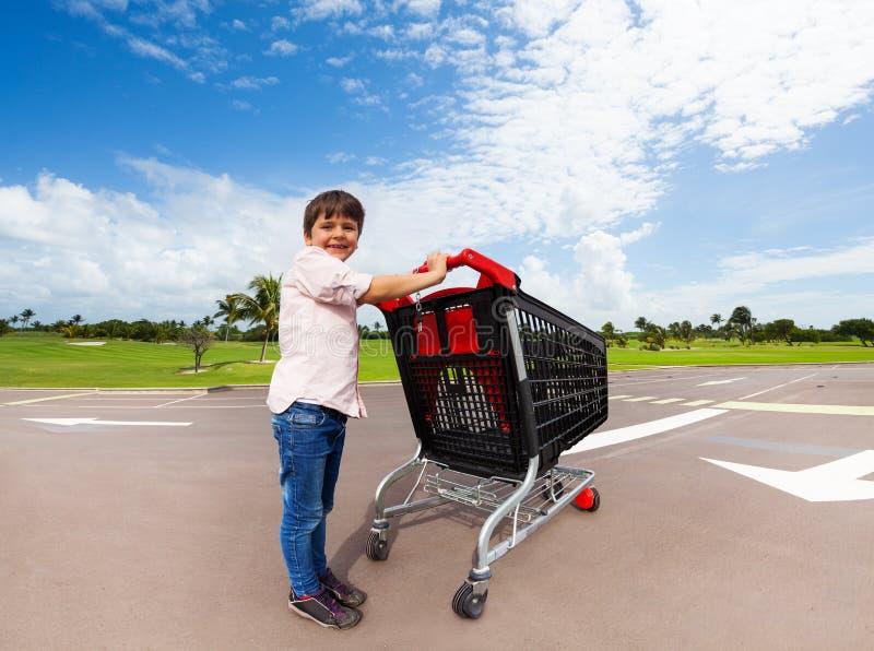 Petite aide poussant le caddie de supermarché images stock