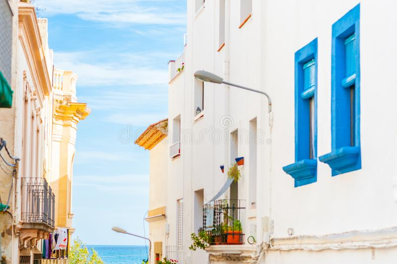 Petite allée dans la ville catalanne de Tossa pendant le jour d'été lumineux en journée avec le ciel bleu et la mer calme image libre de droits