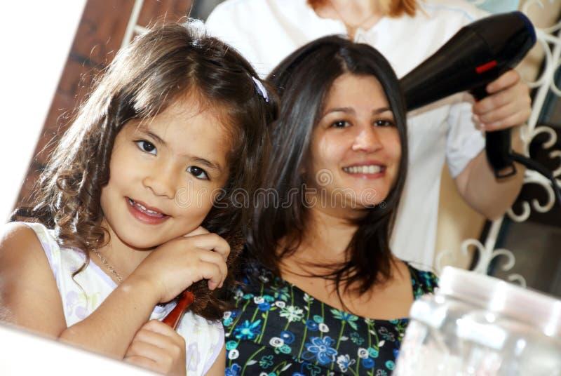 Petite beauté avec la mère dans un salon de coiffure photo stock