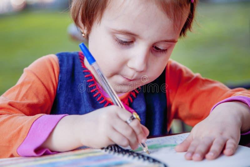 Petite belle écriture de fille dans son éducation de livre, la connaissance, photos libres de droits