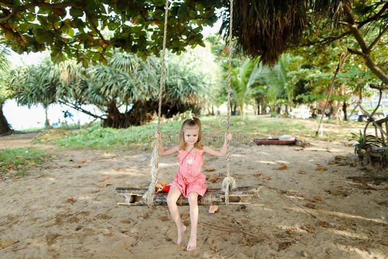 Petite belle équitation de fille sur l'oscillation sur le fond de sable, robe rose de port photos libres de droits