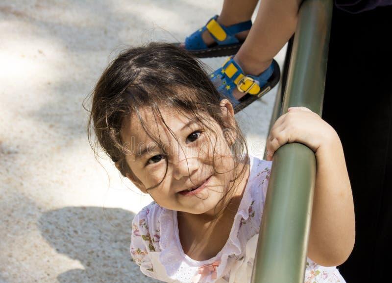 Petite belle fille asiatique de sourire équilibrant sur un poteau images libres de droits