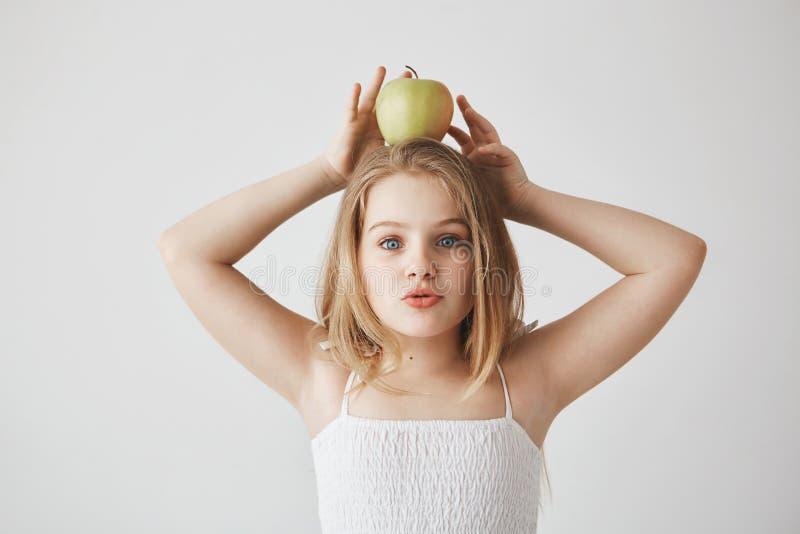 Petite belle fille aux cheveux blonds dans la robe blanche tenant la pomme sur la tête avec des mains, regardant in camera, renda image libre de droits