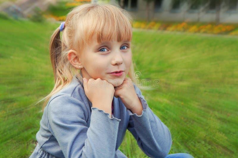 Petite belle fille avec des queues se reposant sur l'herbe en parc image stock