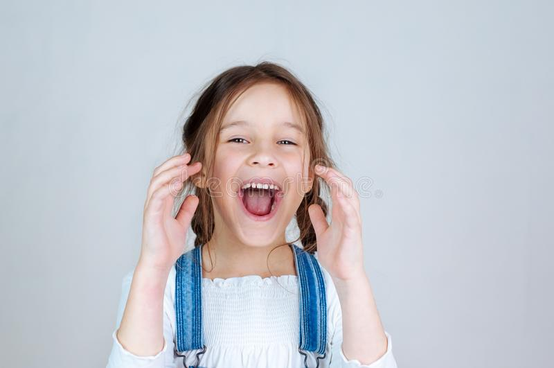 Petite belle fille de portrait ?motif avec des tresses dans des combinaisons de jeans mangeant des morsures tenant une pomme 6-7  photo libre de droits