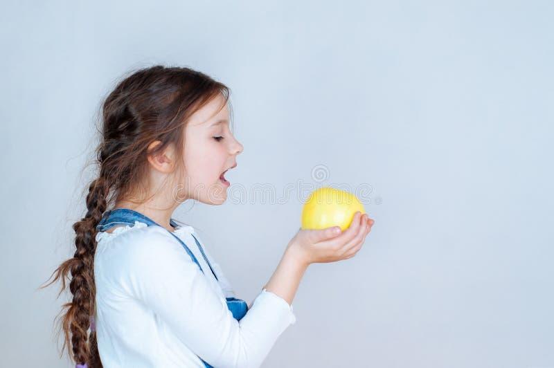 Petite belle fille de portrait ?motif avec des tresses dans des combinaisons de jeans mangeant des morsures tenant une pomme 6-7  images stock