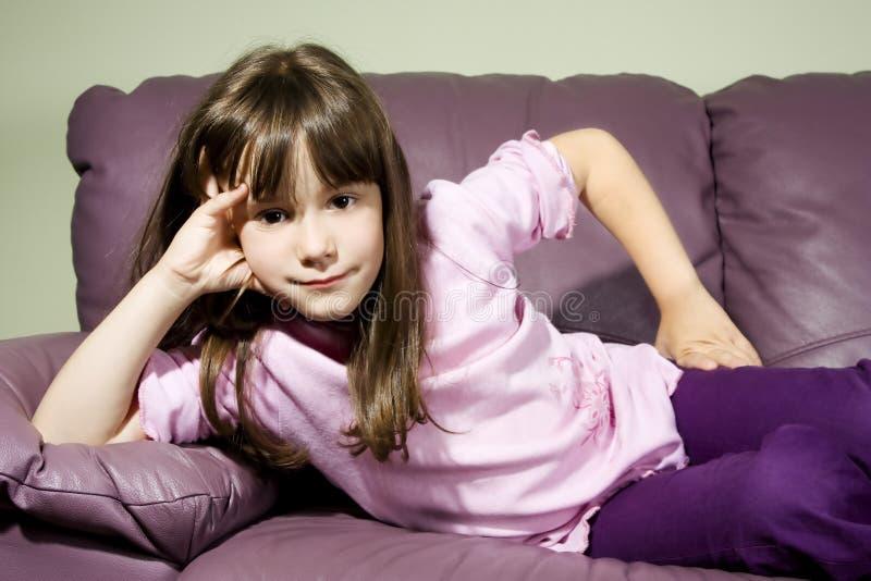 Petite belle fille de sourire posant sur le sofa image stock