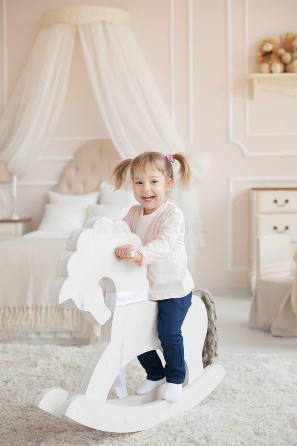 Petite belle fille de sourire sur le cheval en bois de jouet à l'intérieur d'une salle d'enfant photos libres de droits