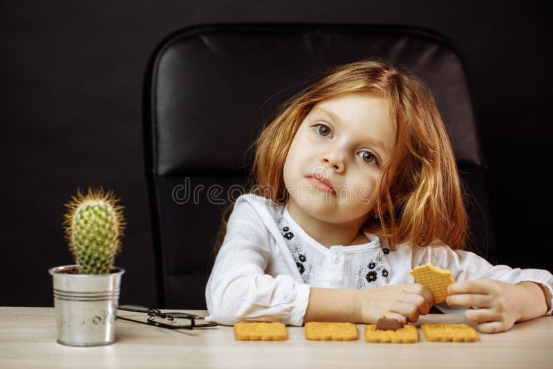 Petite belle fille s'asseyant à la fin blanche de table vers le haut du portrait image stock