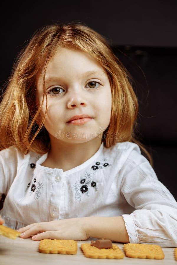 Petite belle fille s'asseyant à la fin blanche de table vers le haut du portrait images stock