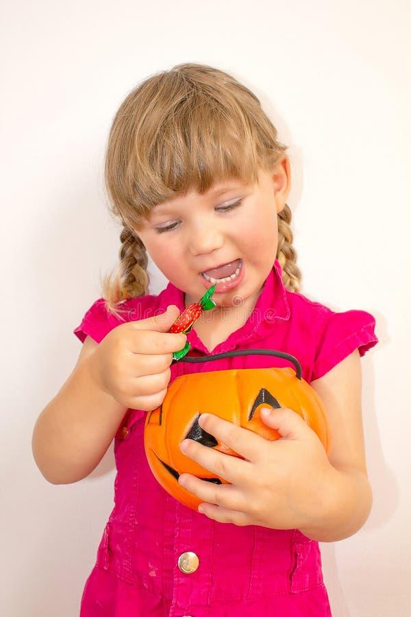 Petite belle fille tenant le potiron avec des bonbons dans des mains, Halloween images libres de droits