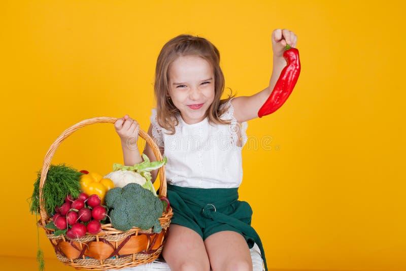 Petite belle fille tenant un panier de fruit frais et de nourriture saine de légumes images libres de droits
