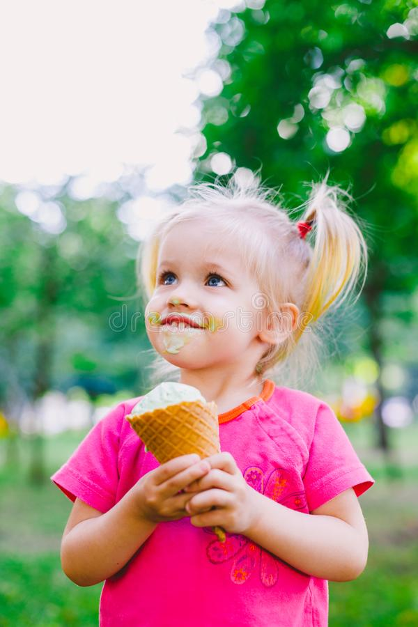 Petite blonde drôle de fille mangeant la crème glacée bleue douce dans une tasse de gaufre sur un fond vert d'été en parc enduit  photo libre de droits