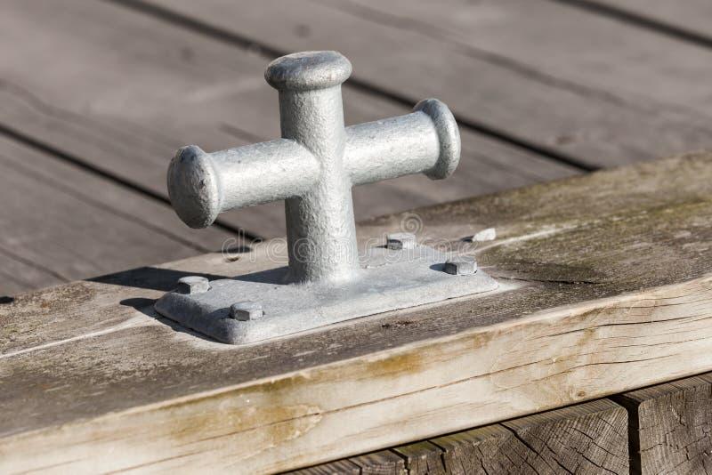 Petite borne grise d'amarrage sur le pilier en bois photo stock