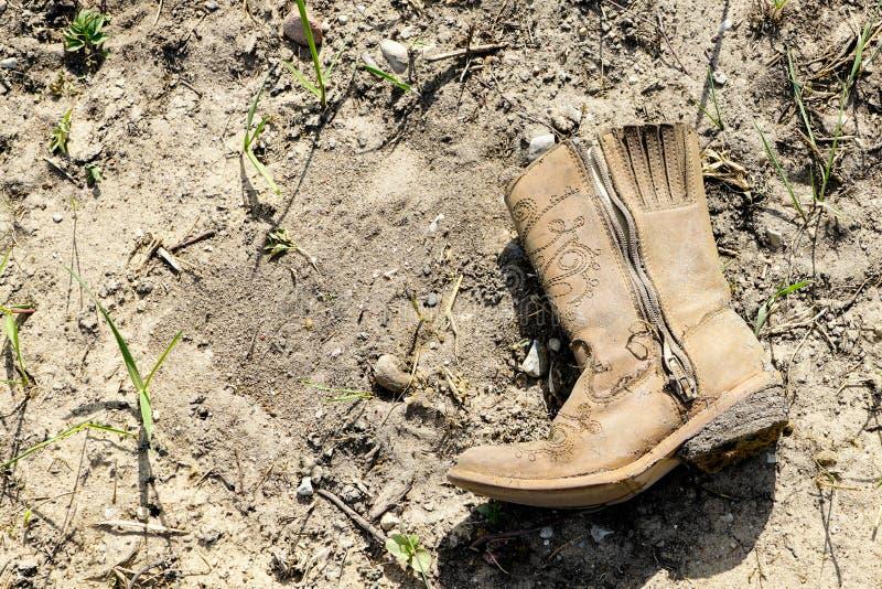 Petite botte de cowboy occidentale sale sur la terre sèche image libre de droits