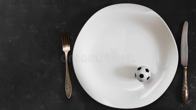Petite boule du football du plat blanc avec la fourchette et du couteau sur le fond texturis? de tableau Horizontal avec l'espace image libre de droits