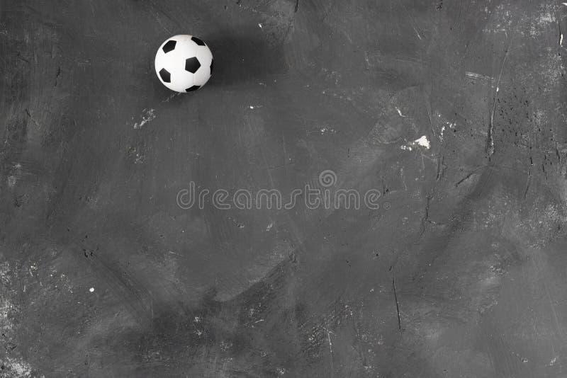 Petite boule du football sur le fond texturisé noir de tableau avec l'espace de copie pour le texte et la conception Vue sup?rieu photographie stock