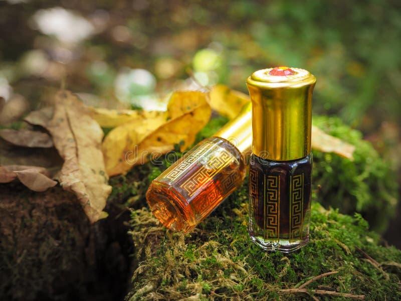 Petite bouteille non-ouverte avec le contenu sur le fond naturel vert Une petite bouteille d'huile d'agarwood au backgroun vert n photo stock