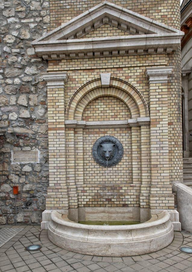 Petite brique et fontaine de marbre avec la tête de l'ours faisant saillie du mur, près de Royal Palace, Budapest, Hongrie images stock