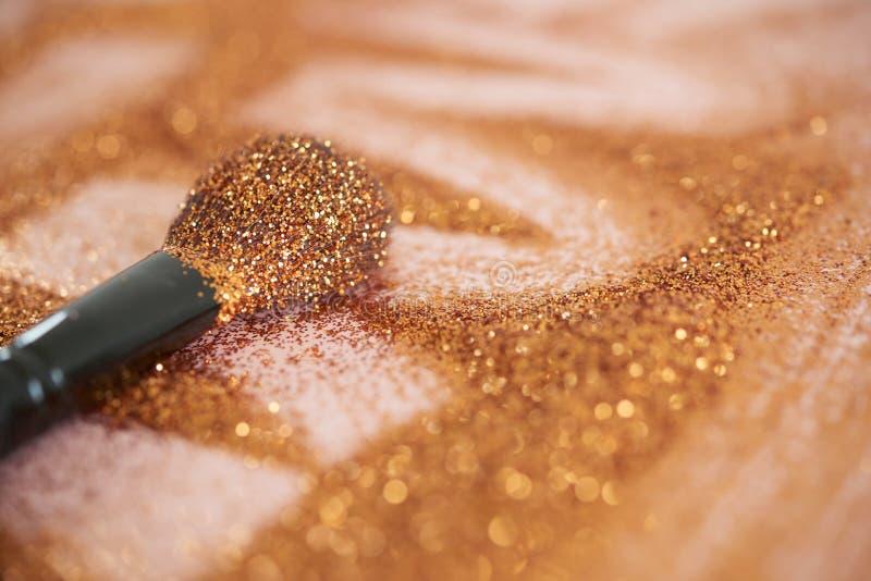 Petite brosse de maquillage couverte de scintillement d'or images stock