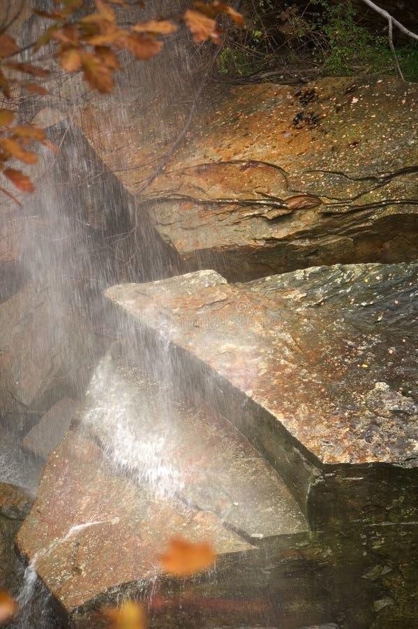 Petite cascade à écriture ligne par ligne, grandes roches photos stock