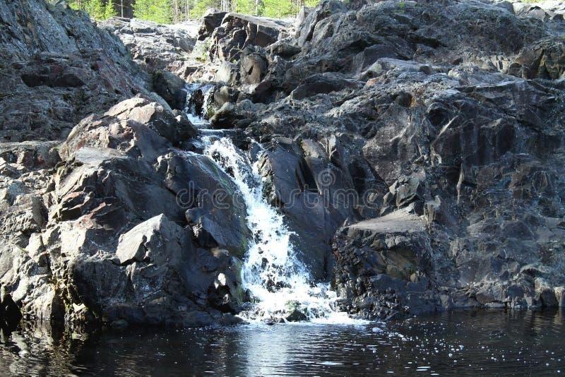 Petite cascade en Carélie dans la forêt avec des roches images libres de droits