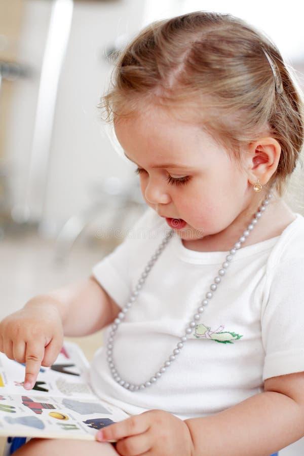 Petite chéri affichant un livre image libre de droits
