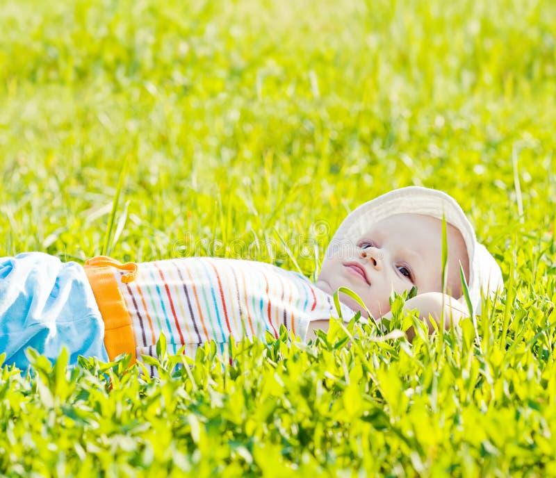 Petite chéri rêvante s'étendant sur l'herbe photographie stock