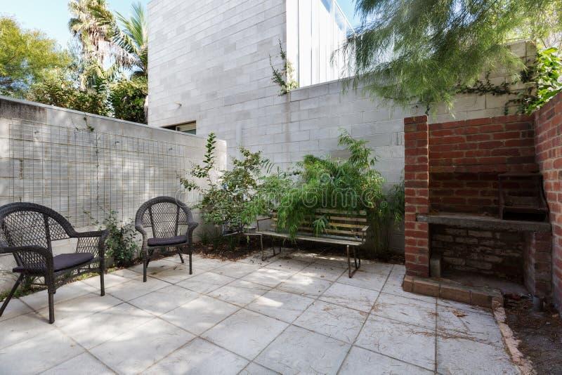 Petite cour d'appartement avec le pavage et les chaises extérieures de canne image stock