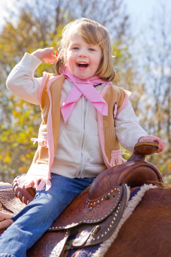 Petite cow-girl montant un cheval photo stock