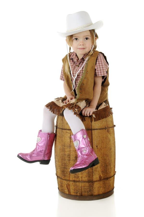 Petite cow-girl s'asseyant assez photo libre de droits