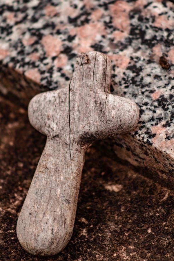Petite croix en bois sur la pierre tombale image libre de droits
