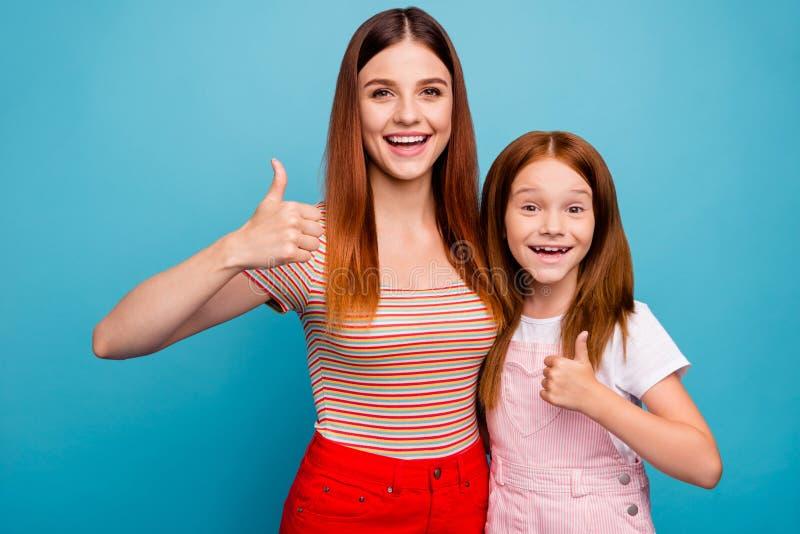 Petite dame rusée enthousiaste et sa maman approuvant la bonne qualité du produit pour porter le fond bleu d'isolement de vêtemen photo libre de droits
