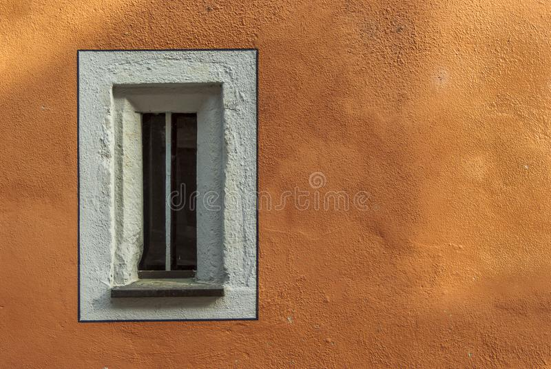 Petite fenêtre étroite dans un vieux bâtiment reconstitué avec la nouvelle façade peinte images libres de droits