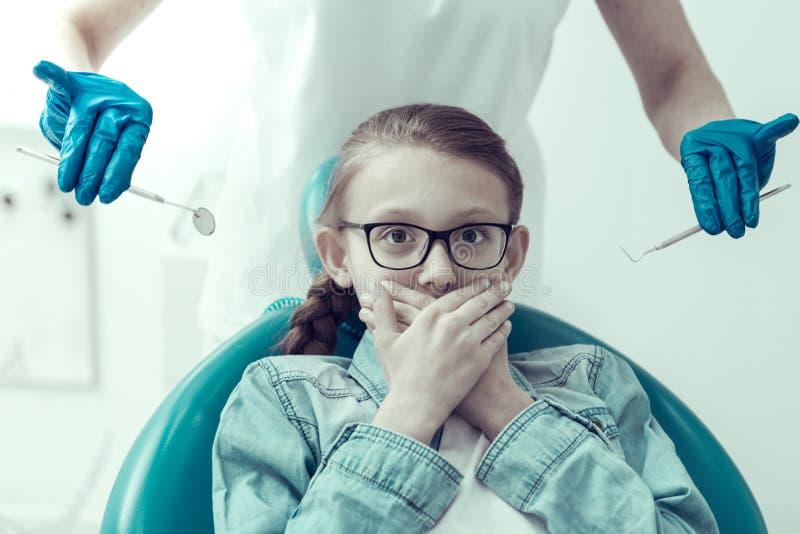 Petite fermeture patiente effrayée sa bouche avec deux mains image stock