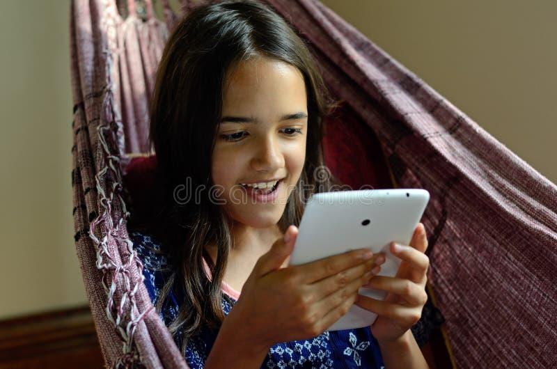 Petite fille à l'aide d'un comprimé dans un hamac photo stock