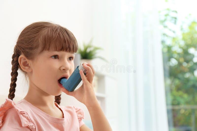 Petite fille à l'aide de l'inhalateur d'asthme image stock