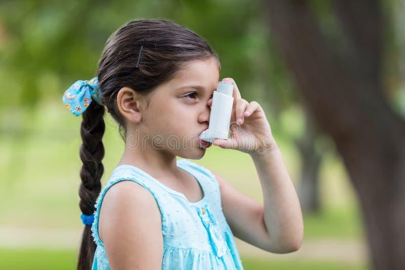 Petite fille à l'aide de son inhalateur photo stock