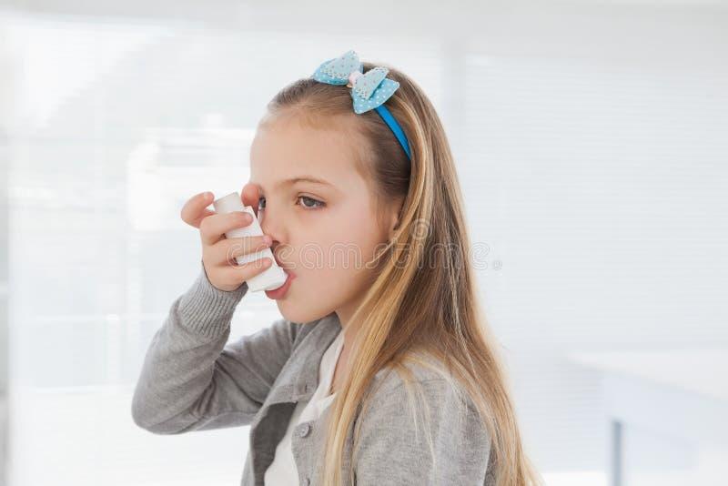 Petite fille à l'aide de son inhalateur photos libres de droits
