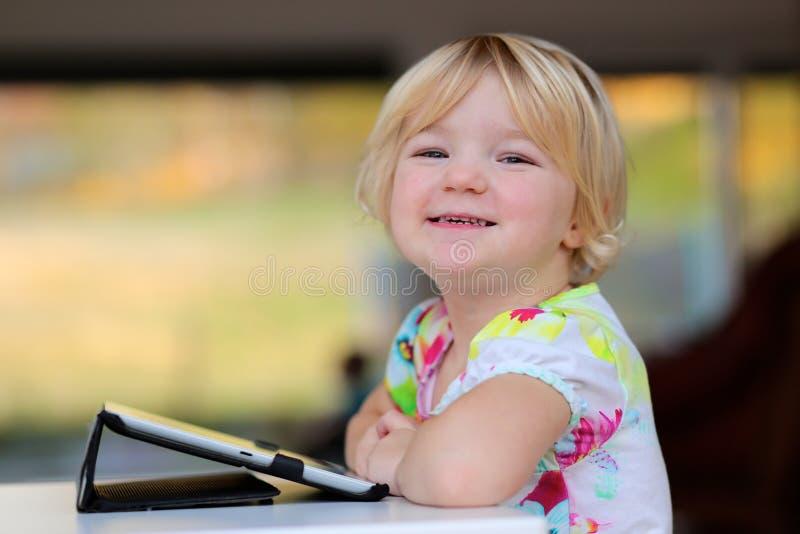 Petite fille à l'aide du PC de comprimé à la maison photo libre de droits