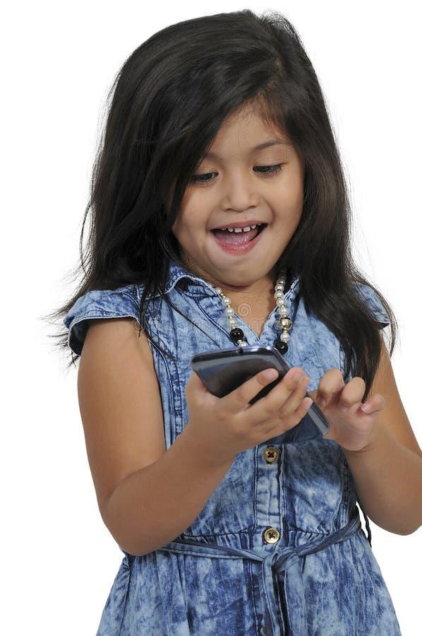 Petite fille à l'aide du téléphone portable images libres de droits
