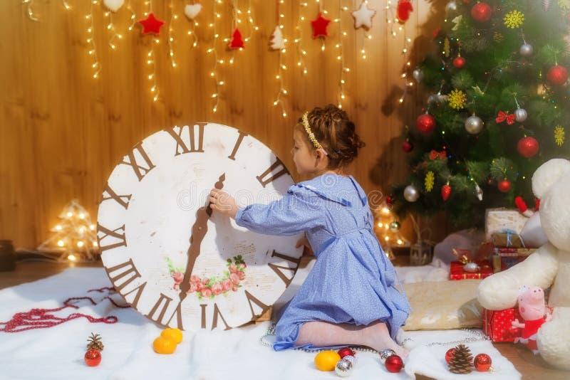Petite fille à l'arbre de Noël avec des jouets et des cadeaux photos stock