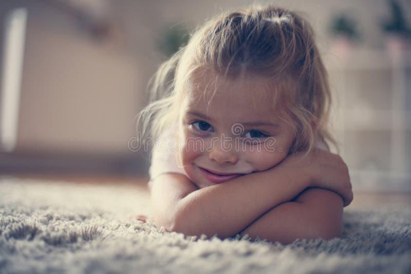 Petite fille à la maison, se trouvant sur le plancher images stock