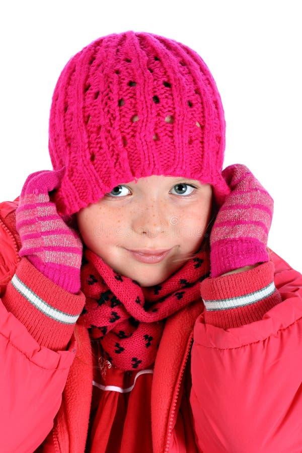 Petite fille étirant son capuchon de l'hiver au-dessus de blanc photographie stock