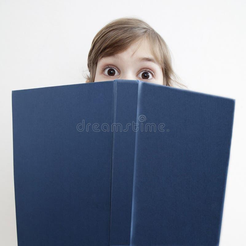 Petite fille étonnée avec le livre images libres de droits