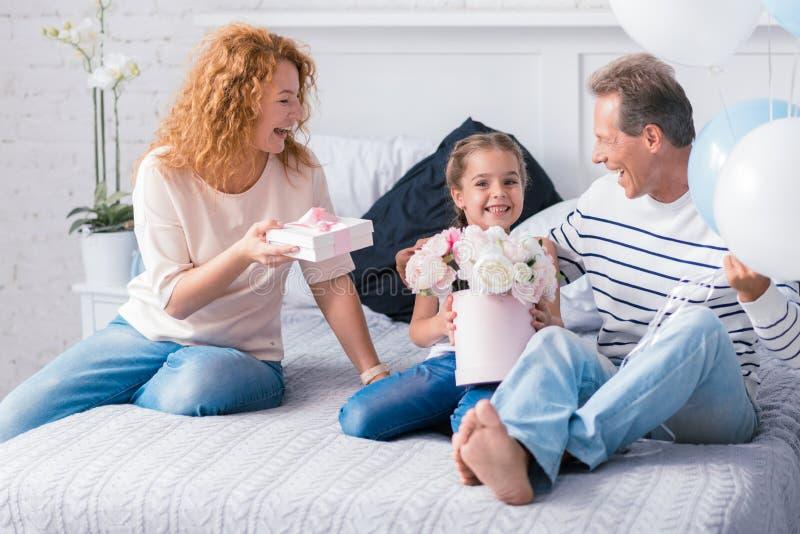 Petite fille étonnée obtenant des présents de ses grands-parents photo libre de droits