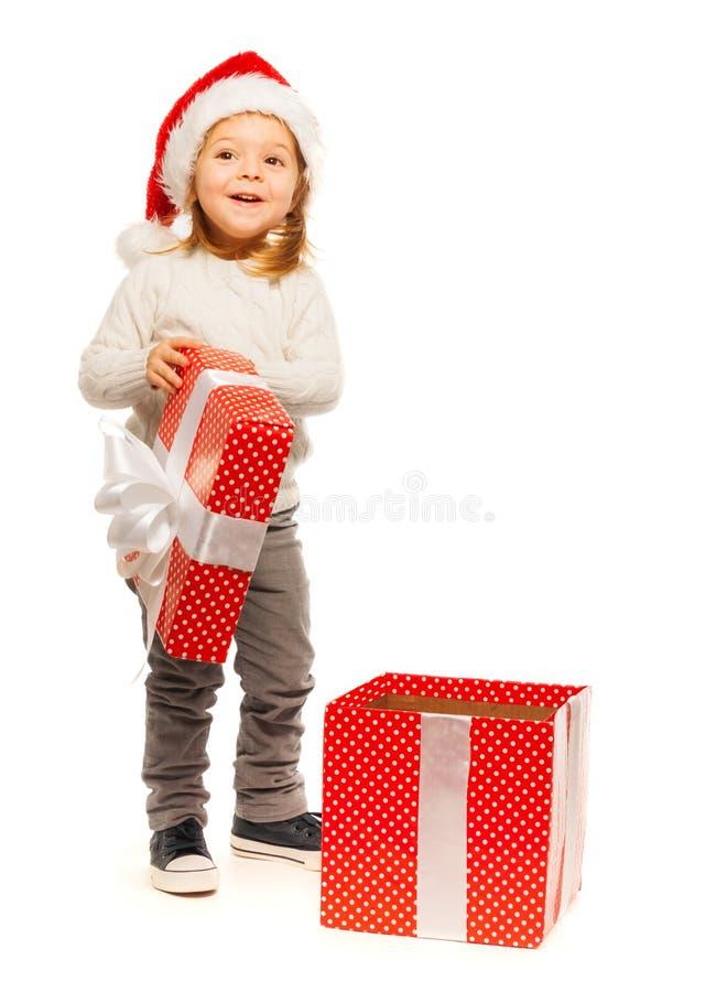 Petite fille étonnée ouvrant son présent photographie stock