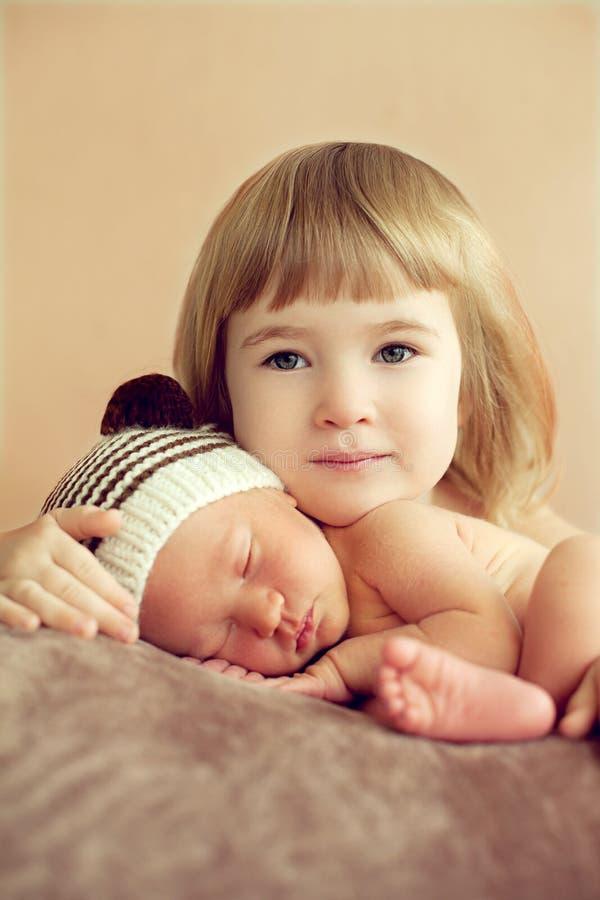 Petite fille étreignant son frère de sommeil nouveau-né Pour l'amour o images stock