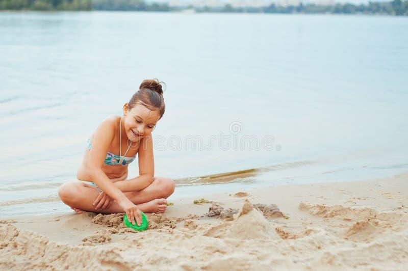 Petite fille adorable établissant un sandcastlle au bord de la mer images libres de droits