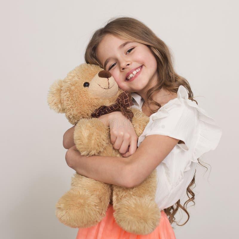 Petite fille adorable étreignant l'ours de nounours images libres de droits